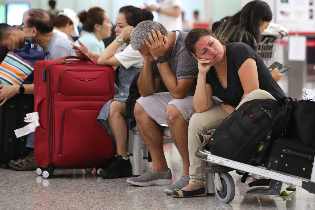 Tourists stranded at Hong Kong International Airport sit and wait for information after 180 departures were cancelled on Monday because of protests. Photo: Sam Tsang