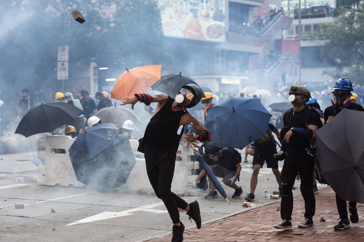 Protesters throw bricks at Hong Kong police, who fired tear gas at them during clashes in Wong Tai Shin area on 5 August 2019. Photo: EPA-EFE