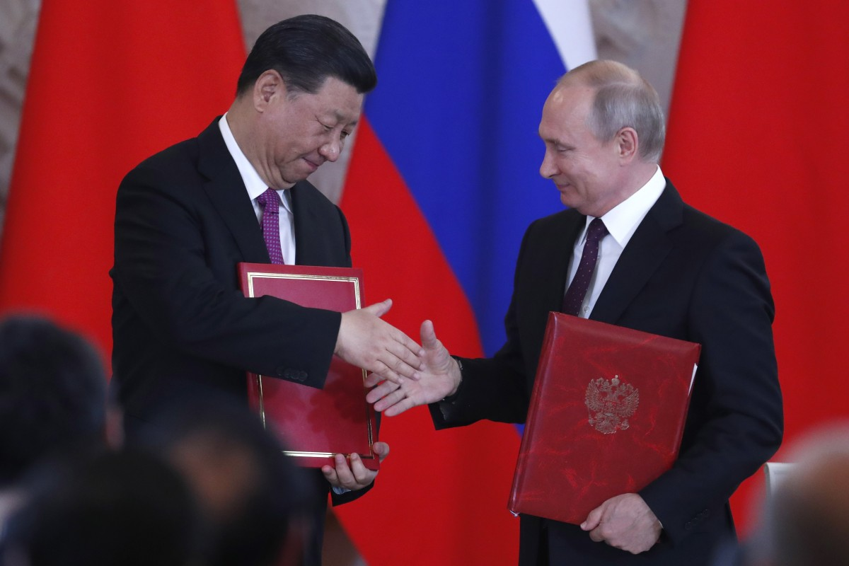 Chinese President Xi Jinping and Russian President Vladimir Putin shake hands during a signing ceremony after their talks at the Kremlin in Moscow on June 5. Photo: EPA-EFE