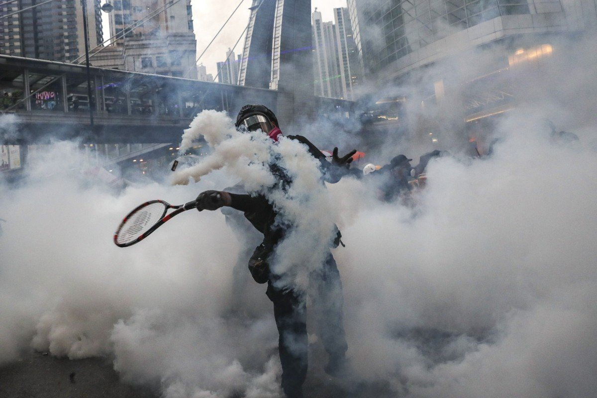 An anti-government protester uses a tennis racket to return a canister fired by police in clouds of tear gas on Yeung Uk Road on August 25. Photo: Sam Tsang