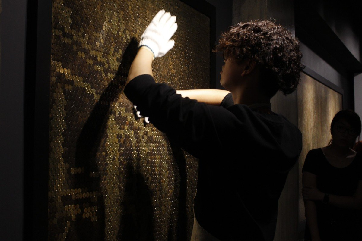 Giraffe Leung rubs a panel made of 20-cent coins with chemical solutions to create an image of Hong Kong at La Galerie Paris 1839 in Central. Photo: Snow Xia