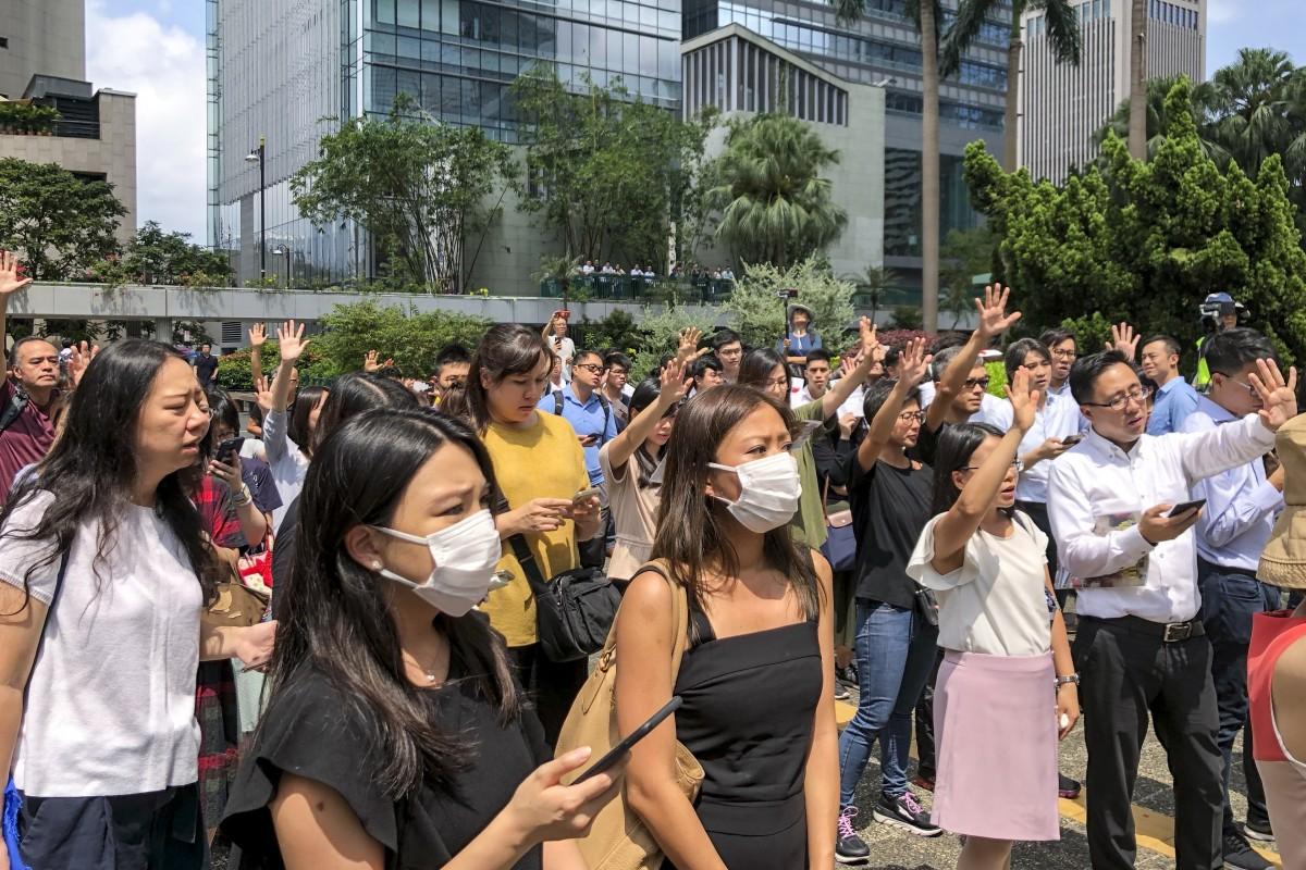 Office workers join singing flash mob on their lunch break as part of Hong Kong protests throughout...