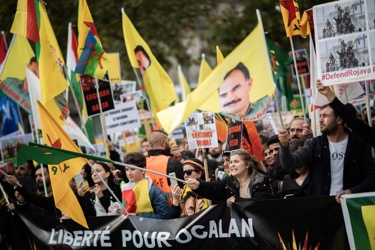 People hold pro-Kurd flags and banner in Paris on October 12. Photo: AFP