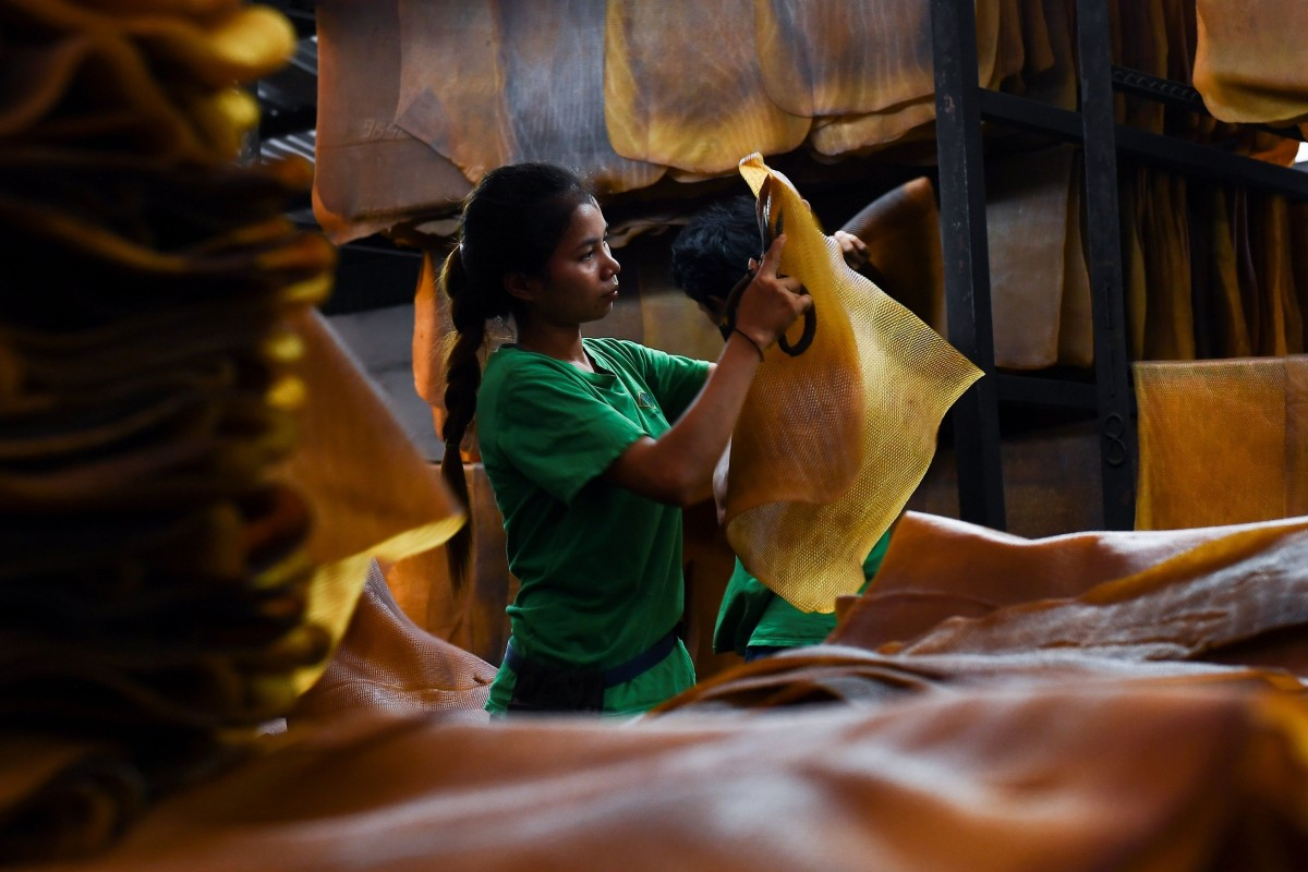 A Thai worker cuts out stains from a raw rubber sheet at a factory in Rayong province. File photo: AFP