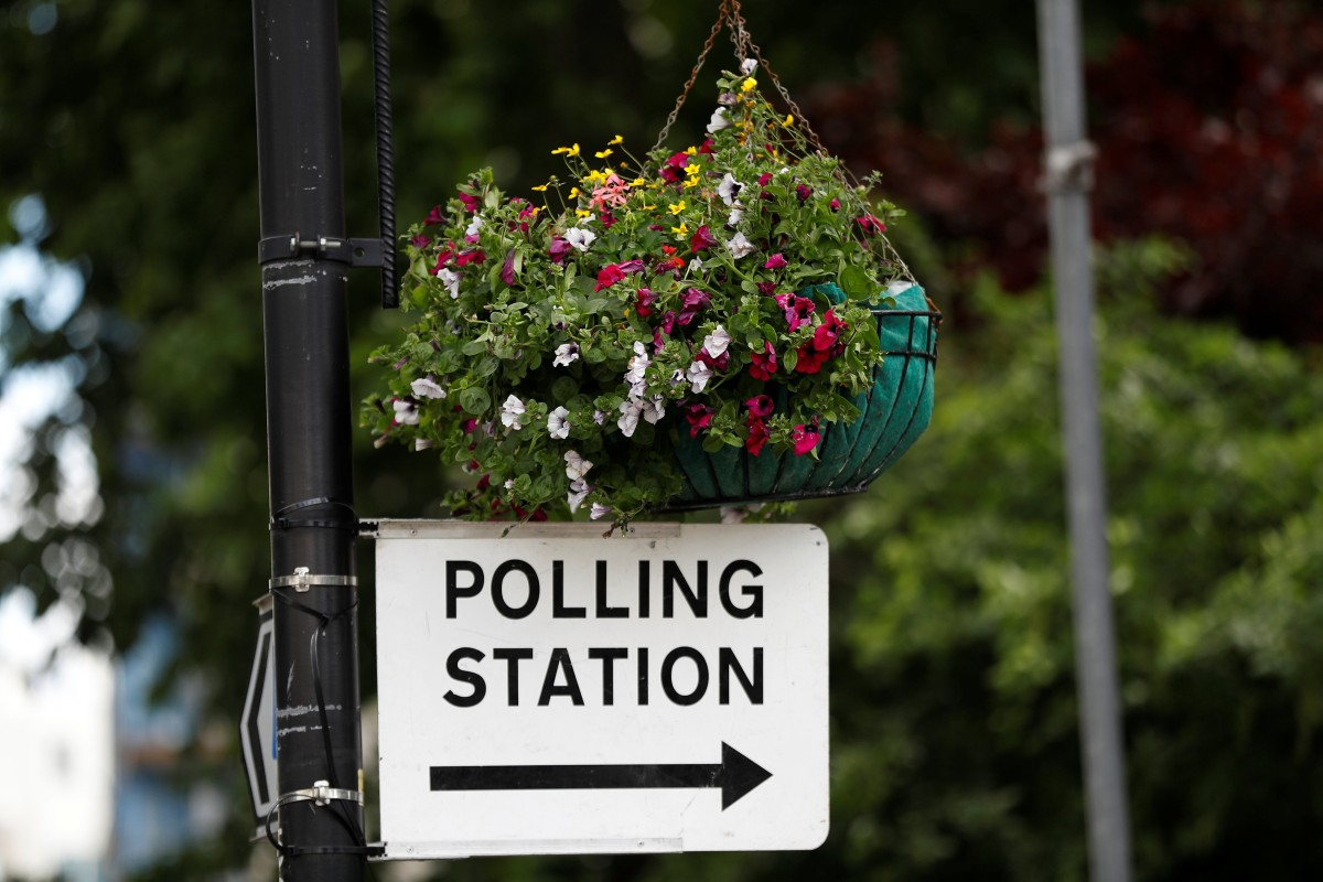 A sign to a polling station hangs from a lamp post in central London. Photo: Reuters