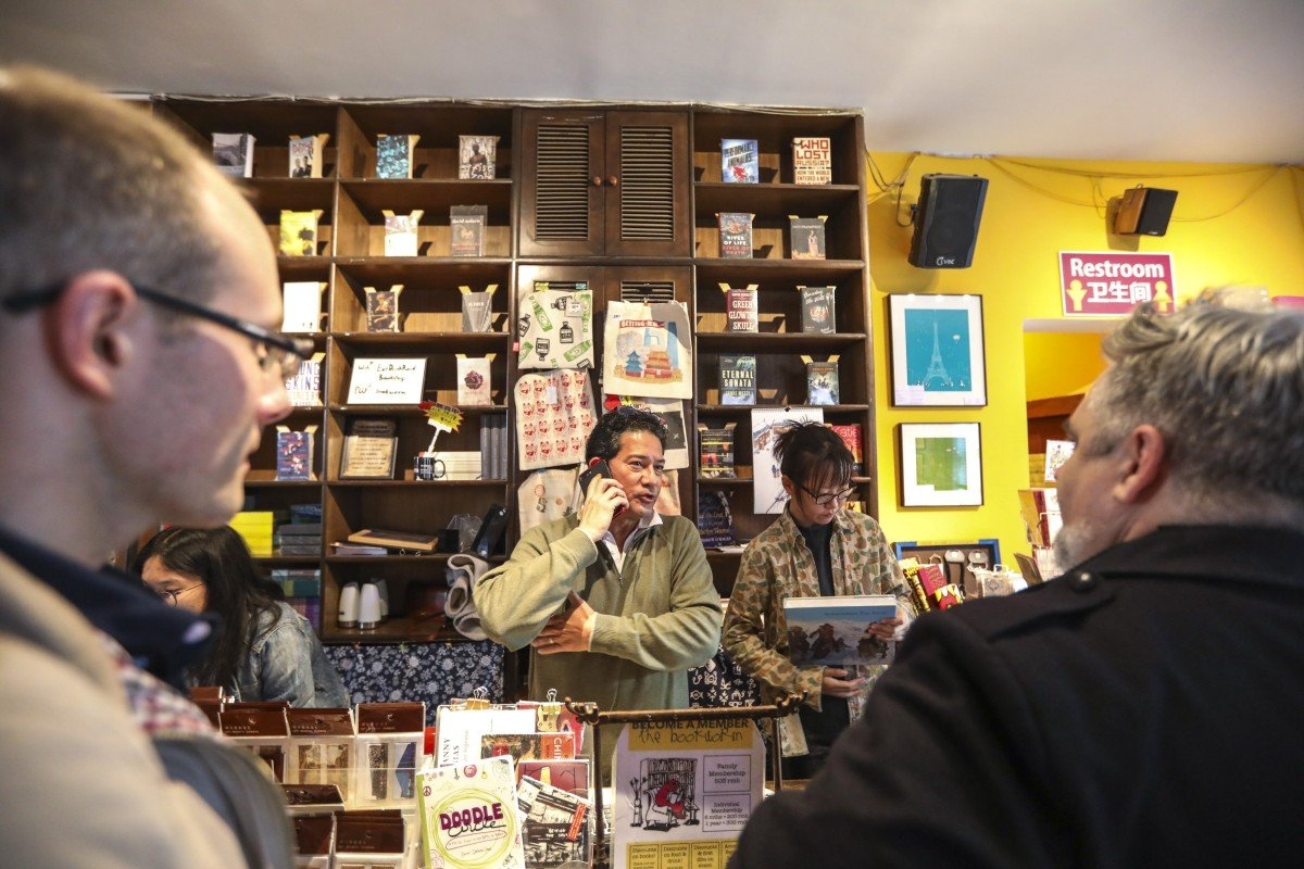 David Cantalupo, co-founder of The Bookworm, takes a phone call at the bookstore in Beijing on Tuesday as customers look on. The store, a cornerstone of the expatriate literary community in the Chinese capital, announced it would close on November 11 having been unable to renew its lease. Photo: Simon Song