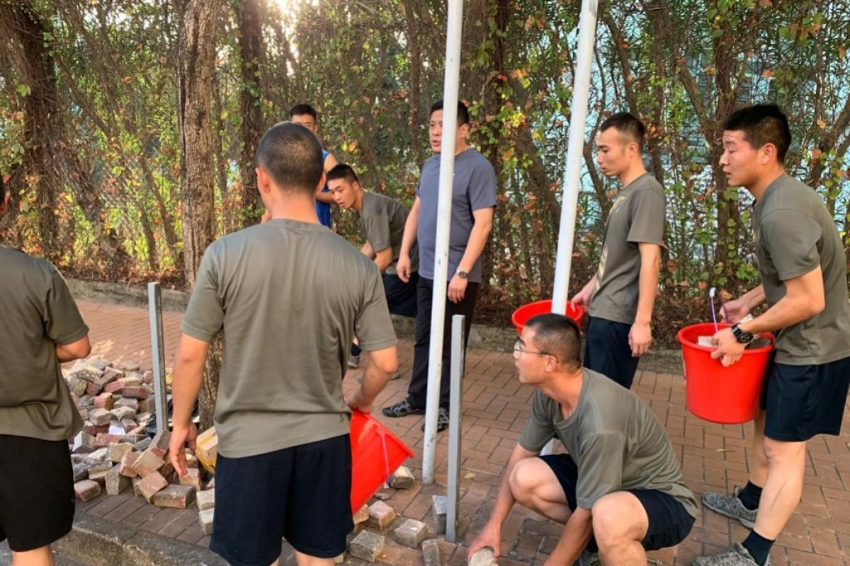 PLA soldiers sent onto streets of Hong Kong for first time since protests began – to help clear roadblocks...
