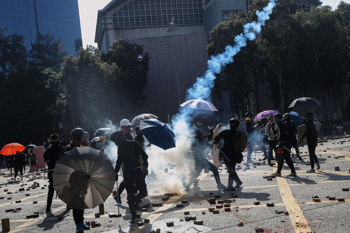 Police fire tear gas as Hong Kong protesters attack crowd trying to clear roadblocks near Polytechnic...