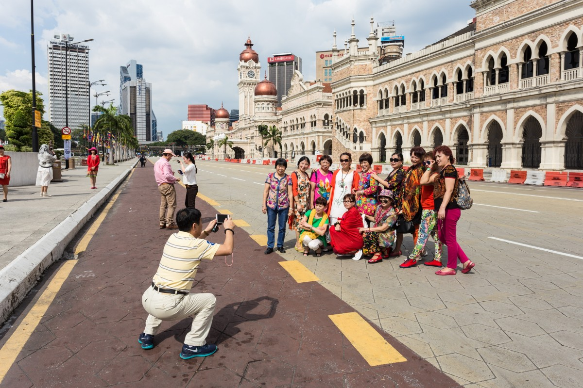 A group of Chinese tourists pose for a photograph in front of the Sultan Abdul Samad Building, in Kuala Lumpur, Malaysia. Photo: Shutterstock