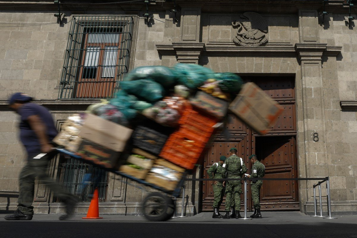 A man pulls a cart full of merchandise past the National Palace. Photo: AP Photo