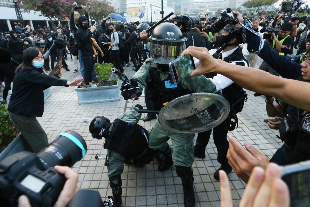 A police officer draws his revolver and points it at the crowd at a rally in Central. Photo: Handout