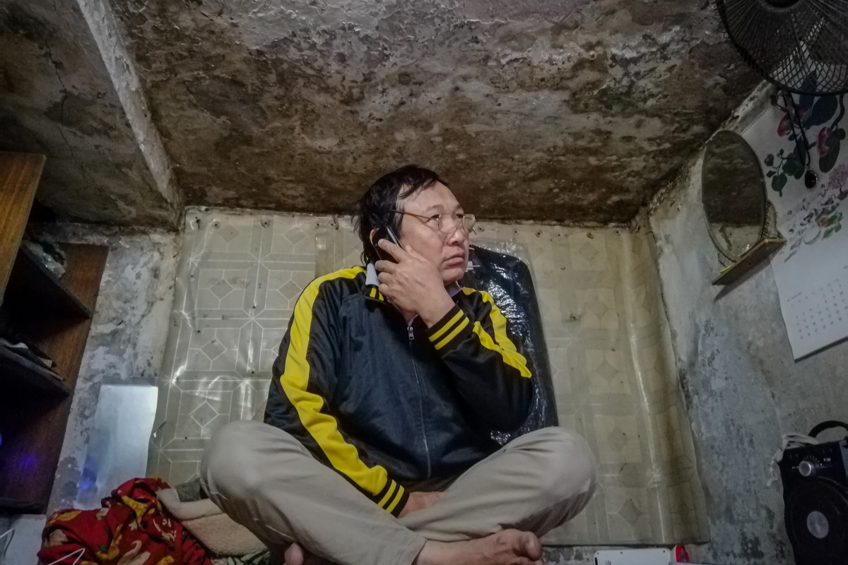 Hoang Van Xuan in the 5-square-metre mouldy attic that he calls his home. He works as a delivery man and motorbike taxi driver, but as the popularity of bike-sharing platforms explodes, he can barely make ends meet. Photo: Sen Nguyen