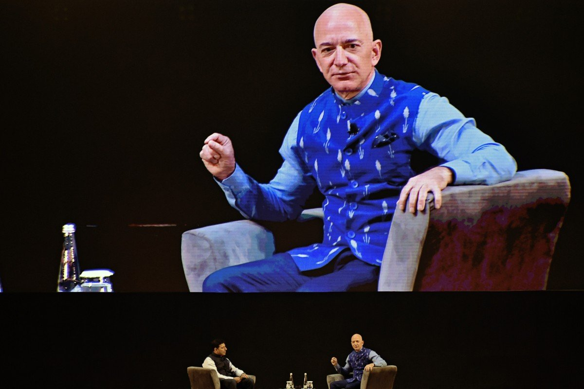 Jeff Bezos, founder and chief executive of Amazon.com, right, speaks as Amit Agarwal, head of Amazon India, listens during the opening session of the company's Sambhav event in New Delhi on January 15. Photo: Bloomberg