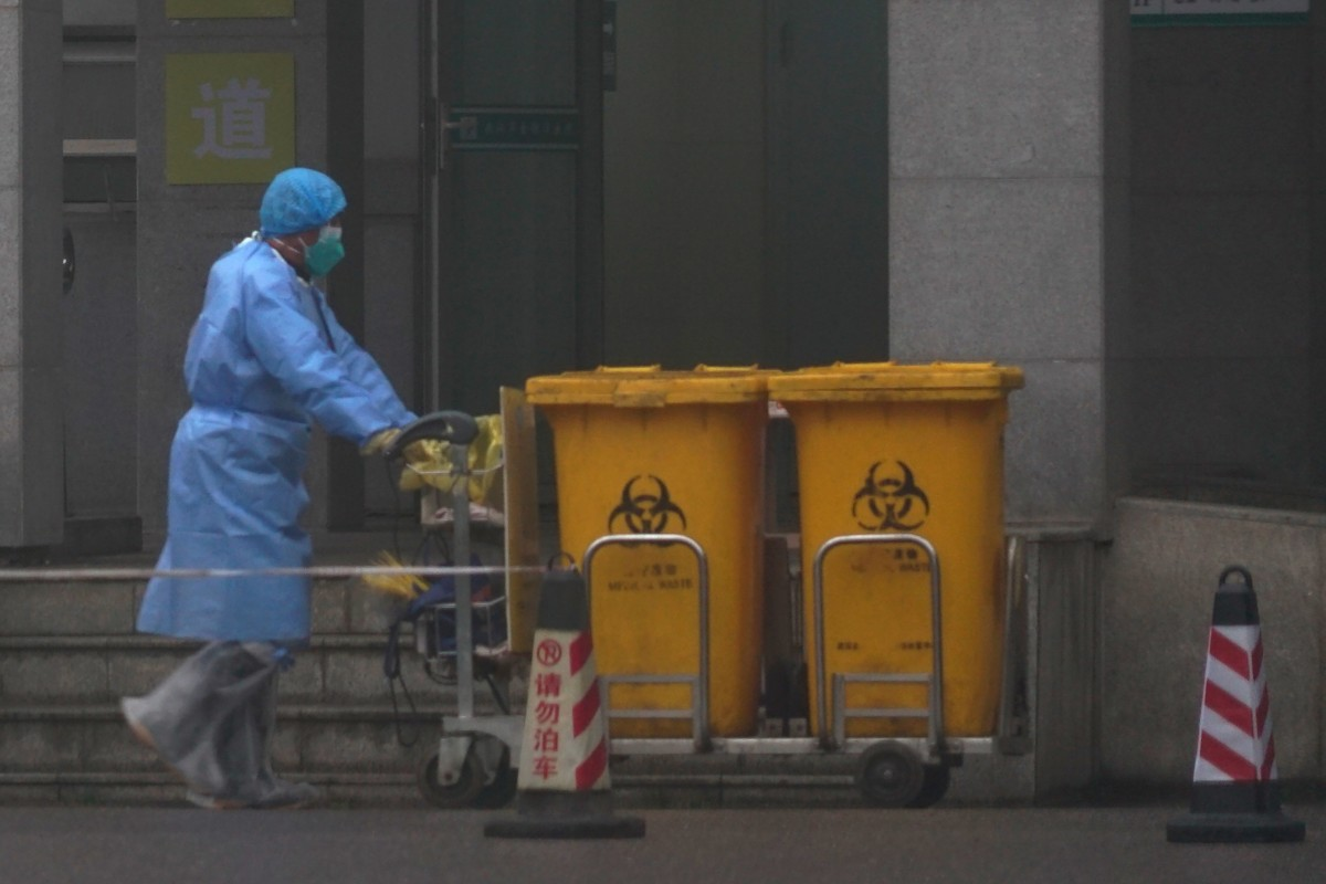 Staff move bio-waste containers past the entrance of the Wuhan Medical Treatment Centre in China, where some people infected with the new virus are being treated. Photo: AP