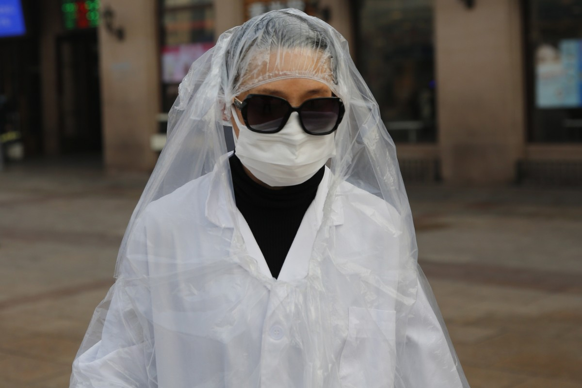 A passenger wearing a protective mask covers her body with plastic bags as protection from the coronavirus at a Beijing railway station on Tuesday. Photo: EPA-EFE