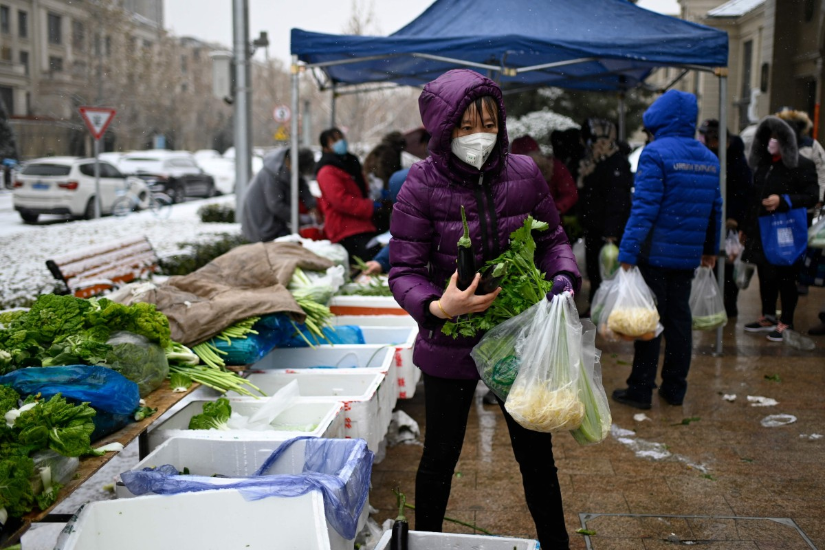 A woman wearing a mask buys vegetables at an open market in Beijing on February 2, after an outbreak of virus similar to the SARS pathogen. Photo: AFP