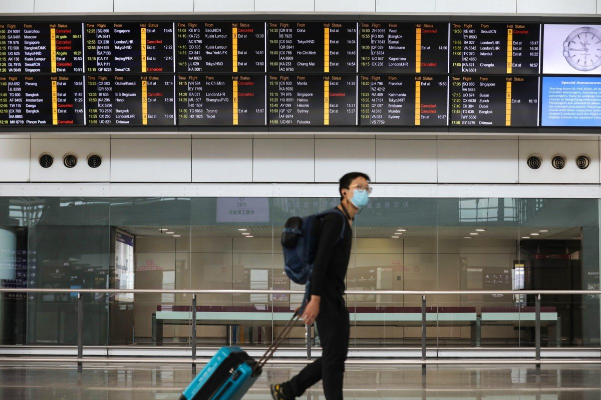Passengers wearing protective masks walk past an information board at Hong Kong International Airport, on the first day of a travel ban on travellers from South Korea. Photo: Winson Wong