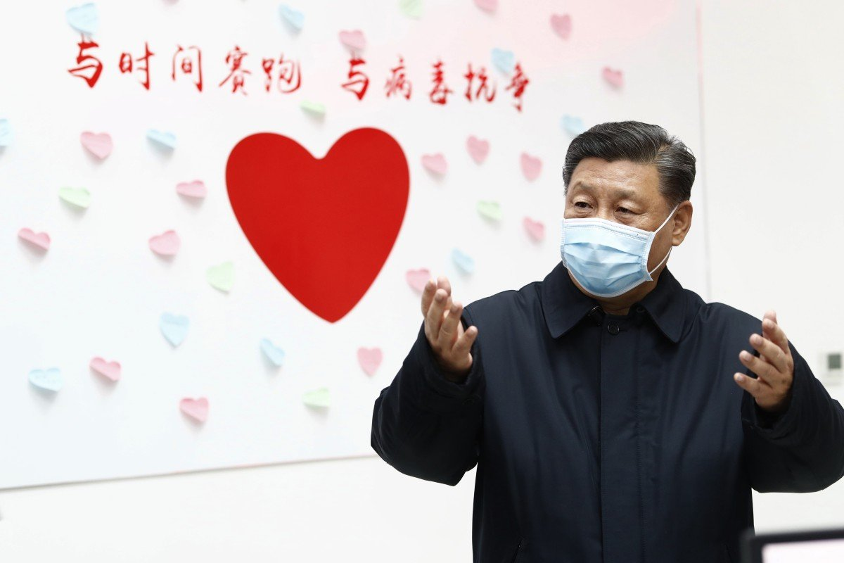 "Chinese President Xi Jinping gestures near a heart-shaped sign and the slogan ""Race against time, fight the virus"" during an inspection of Chaoyang District's centre for disease control and prevention in Beijing on February 10. Photo: Xinhua"