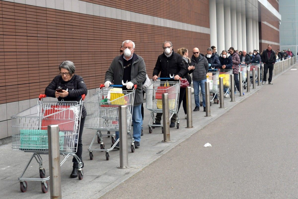 People wearing protective face masks lined up in front of a supermarket in Milan on March 12, 2020. Photo: EPA-EFE