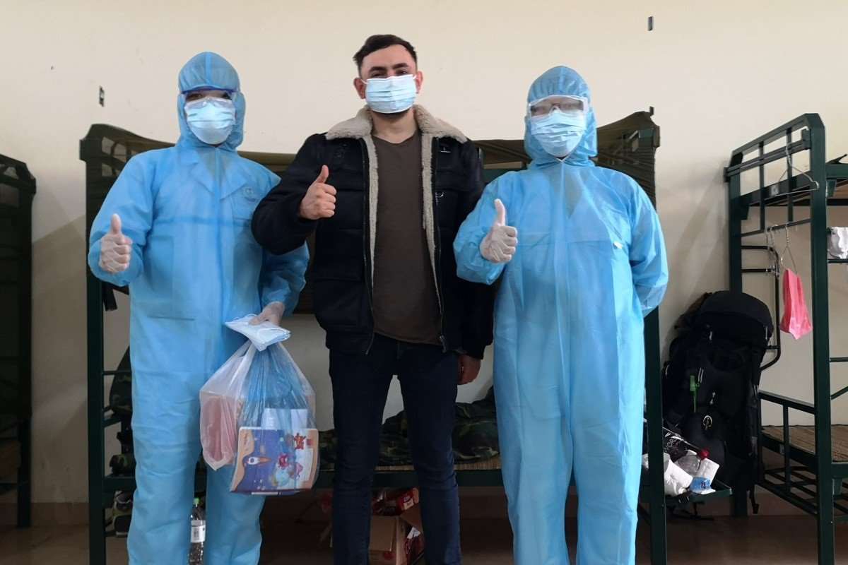 British tourist Gavin Wheeldon raises a thumbs-up with two medical staff in his room at Son Tay Military School quarantine camp in Hanoi. Photo: Gavin Wheeldon