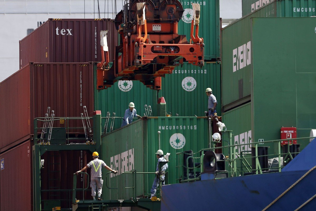 Crew watch as a container is loaded on to a cargo ship in Tokyo. The International Chamber of Shipping estimates that at least 100,000 seafarers a month need to change over from the ships they work on. Photo: Reuters