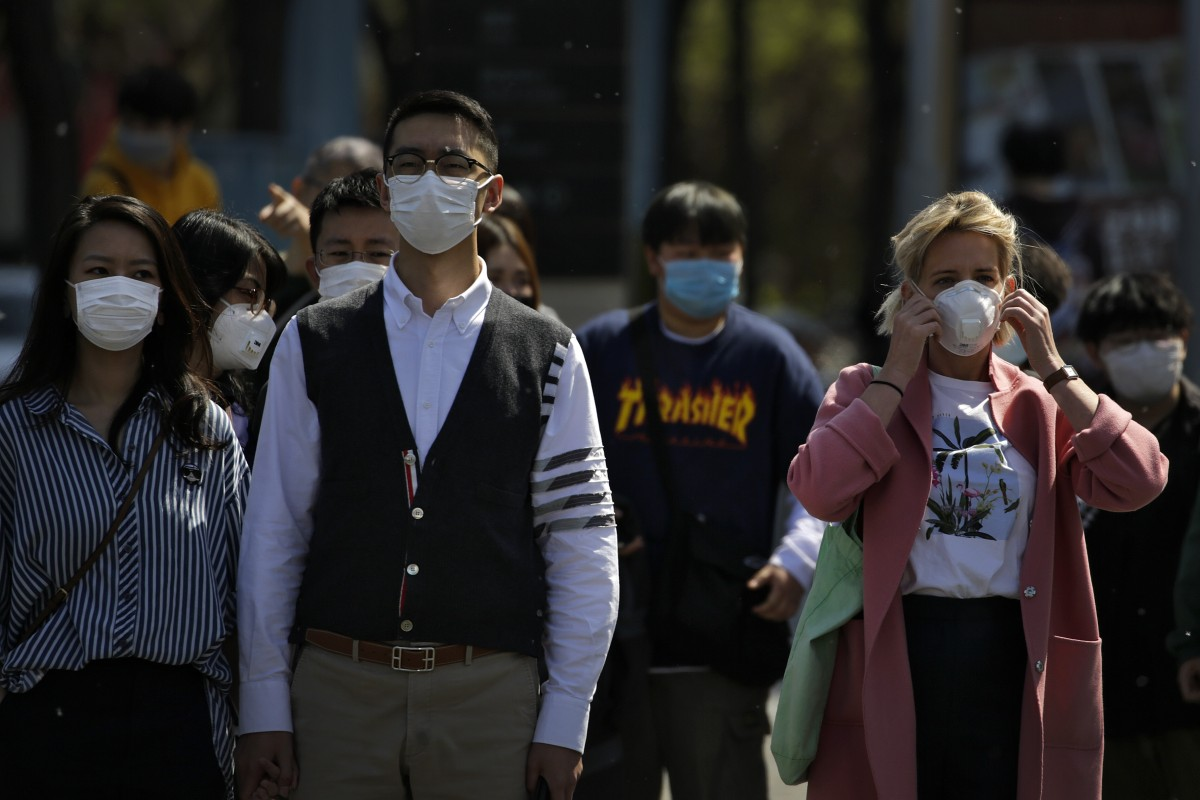 Commuters wear face masks to protect against the spread of new coronavirus as they walk through a subway station in Beijing. As the virus has travelled round the world, masks have become one of the essential commodities of 2020. Photo: AP