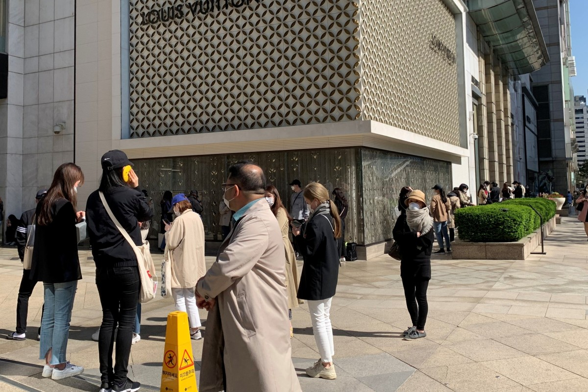 People practise social distancing as they queue to enter the Chanel boutique at a department store in Seoul on Wednesday ahead of price rises on some bags and leather goods. Photo: Reuters