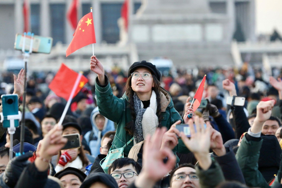 People wave Chinese flags as they gather for a flag-raising ceremony to mark the New Year in Tiananmen Square in Beijing. Photo: Reuters
