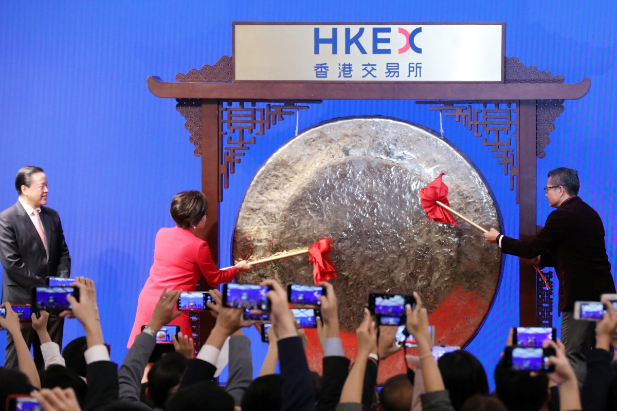 Hong Kong Exchanges and Clearing (HKEx) Chairperson Laura Cha Shih May-lung (left); Hong Kong Financial Secretary Paul Chan Mo-po (right) striking the ceremonial gong on the first trading day of the Lunar New Year on the city's stock exchange on 8 February 2019. Photo: Felix Wong