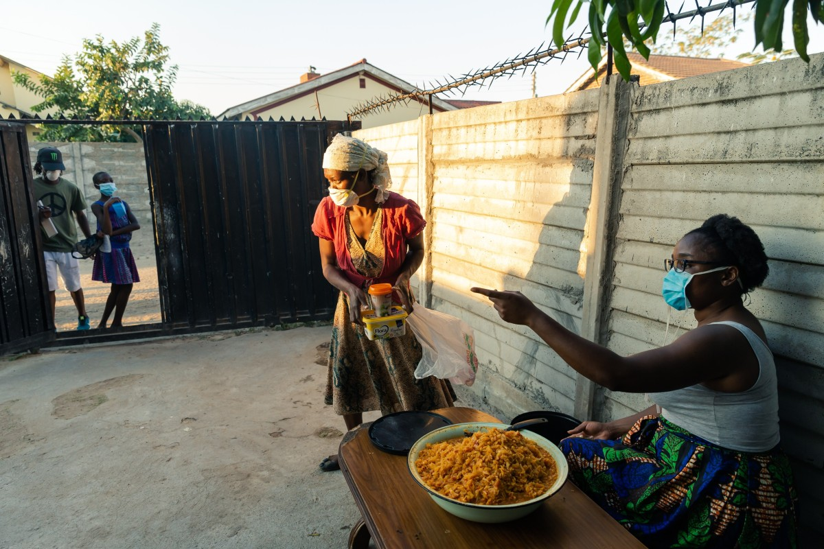 Samantha Murozoki (R) hands a free meal to a woman from her home in Chitungwiza, a satellite town of Zimbabwe's capital Harare. Photo: AFP