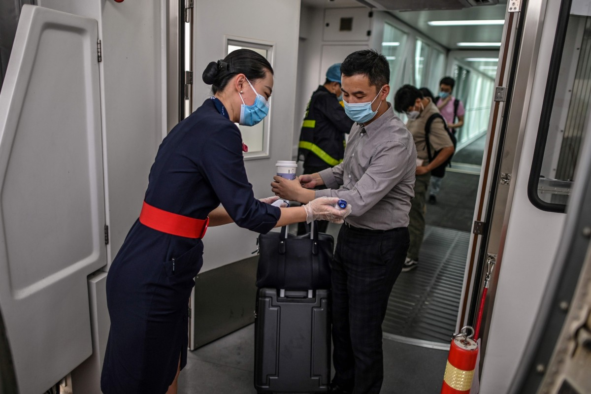 A flight attendant wearing a face mask checks the body temperature of boarding passengers on a plane at Tianhe Airport in Wuhan, China. Photo: AFP