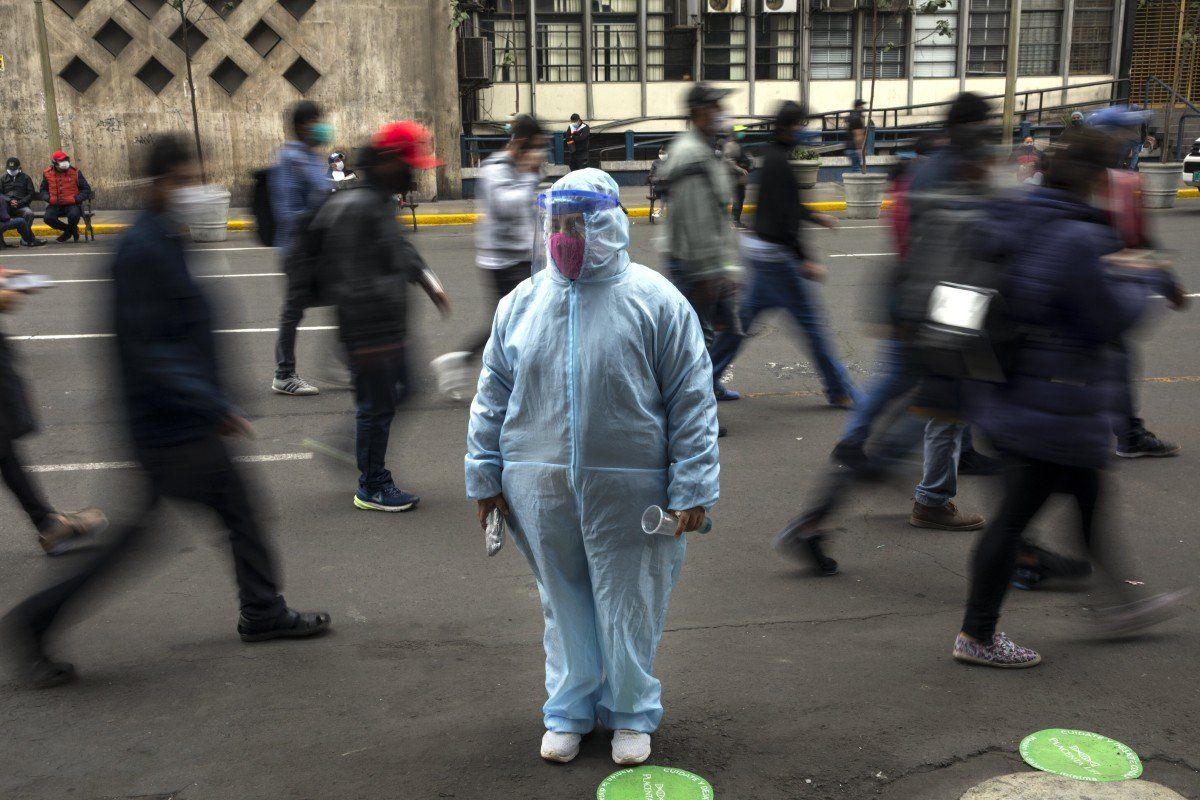 A woman waits outside a shop wearing protective gear due to the Covid-19 pandemic in downtown Lima, Peru on Monday. Photo: AP