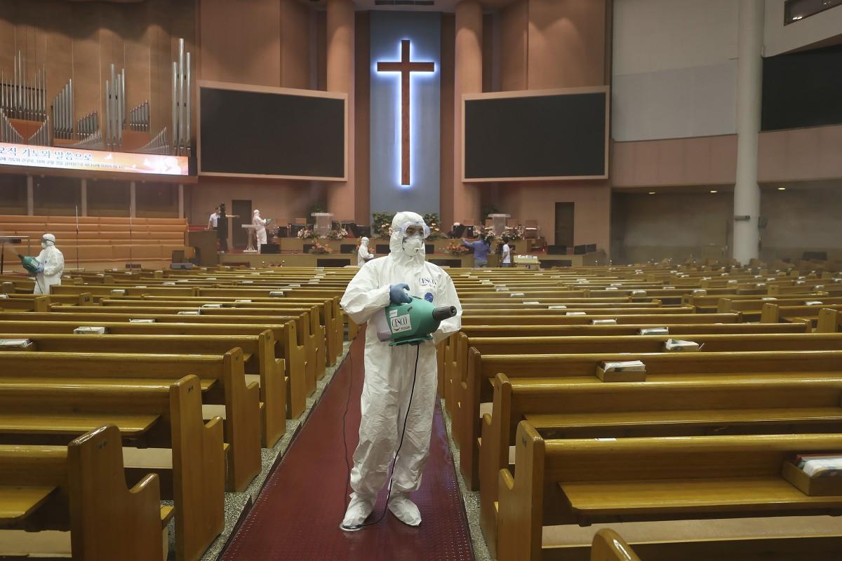 Public officials disinfect a church in South Korea. Photo: AP