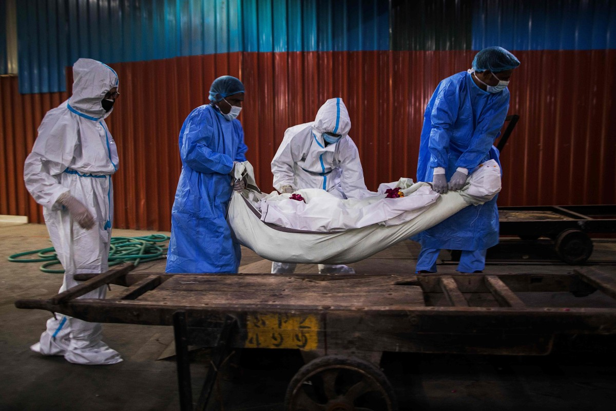 Relatives (in white) along with workers (in blue) wearing PPE help to place the body of a person who died from coronavirus in New Delhi. Photo: AFP
