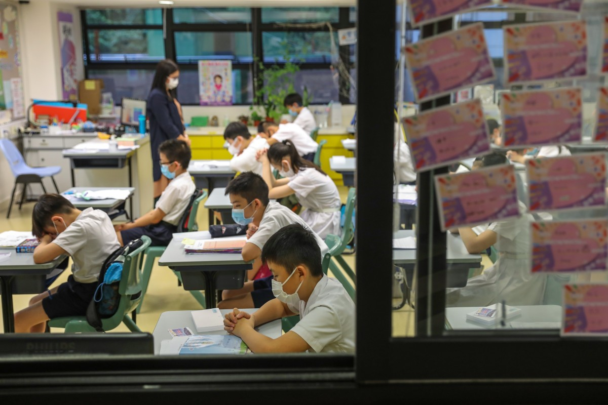 Primary school students in a Wan Chai school pray for the Covid-19 pandemic to ease before class on June 8. Photo: Nora Tam