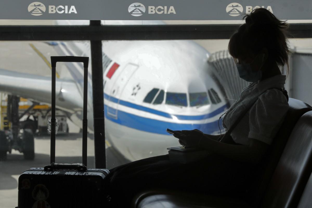 Una mujer que usa una mascarilla para ayudar a frenar la propagación del coronavirus navega por su teléfono inteligente en el Aeropuerto Internacional de Beijing Capital, el 8 de septiembre de 2020. Foto: AP Photo