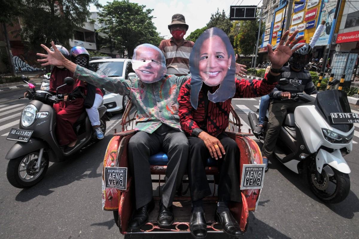 Penduduk lokal yang memakai topeng Joe Biden dan Kamala Harris melambai saat mereka menaiki becak di sepanjang jalan di Solo, Jawa Tengah, Indonesia.  Foto: AFP