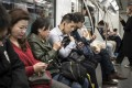 Commuters with their smartphones in Shanghai. (Picture: Qilai Shen/Bloomberg)