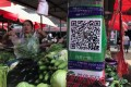 Mobile payments are so ubiquitous in China that even outdoor markets make sure their QR codes are prominently displayed for easy payment. (Picture: Simon Song/SCMP)