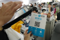 A customer scanning an Alipay payment code held by a flight attendant on a plane bound for Helsinki from Beijing. (Picture: Zhang Xuan/Xinhua)