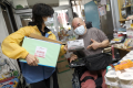 A homebound disabled person receives a care pack funded by The Hong Kong Jockey Club through SAHK, a rehabilitation service organisation.