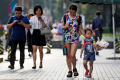 Pedestrians view their smartphones on a sidewalk in Beijing. (Picture: Andy Wong/AP Photo)