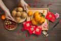 """Flat lay Chinese lunar new year food preparation table top shot. Senior female hand serving a plate of sesame ball dessert on wooden table. Chinese word """"Blessing"""" printed on red packet. Photo: Getty Images"""