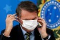 Brazilian President Jair Bolsonaro adjusts his face mask during a news conference in Brasilia, Brazil, on March 18, 2020. Under Biden, Bolsonaro's far-right discourse is likely to fall on deaf ears. Photo: Reuters