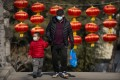 A man and child wear masks in a public park in Beijing. China has not lifted its birth rate more than four years after ending the one-child policy. Photo: AP