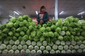 A seller stands behind a pile of vegetables at a market in Beijing, China on April 11, 2016. Photo: EPA