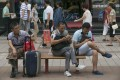 People play with their smartphones at a shopping district in Beijing, China, on July 23, 2014. Photo: EPA
