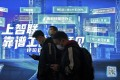 Commuters browse their smartphones as they walk by a mobile phone app advertisement at a subway station in Beijing. Photo: AP