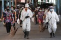 Workers wearing protective suits walks beside residents at a public market during the start of a stricter lockdown in Manila. Photo: AP