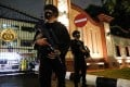 Armed police officers stand guard at the gate of national police headquarters in Jakarta. Photo: Reuters
